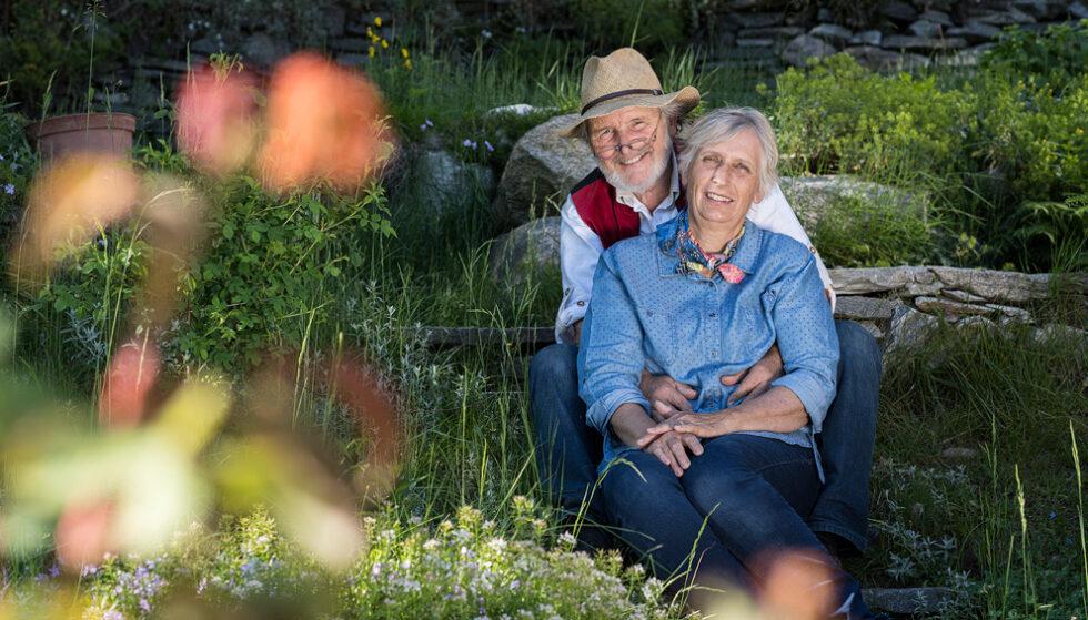 Altes, glückliches Paar sitzt friedlich und lachend in einer Wiese